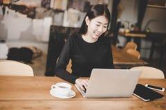使用片剂计算机的企业亚裔少妇与在工作区的财务数据一起使用 免版税库存图片