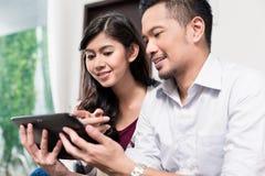 使用片剂计算机的印度尼西亚夫妇在家 库存图片