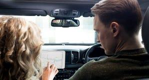 使用片剂计算机的夫妇在汽车 免版税库存图片