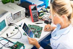 使用片剂计算机的女性电子工程师在实验室 免版税库存图片