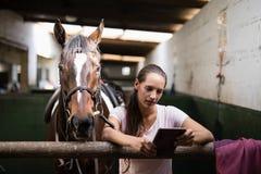 使用片剂计算机的女性骑师,当站立反对马时 免版税库存图片
