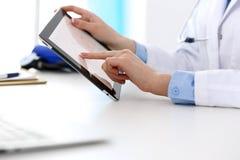 使用片剂计算机的妇女医生,当坐在书桌在医院特写镜头时 心脏科医师检查心脏图 库存图片