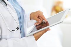使用片剂计算机的妇女医生,当站立直接在医院时 图库摄影