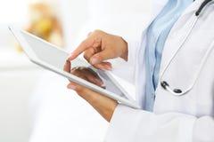 使用片剂计算机的妇女医生,当站立直接在医院时 库存图片