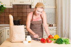 使用片剂计算机的妇女在她的厨房里烹调 图库摄影