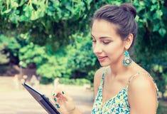 使用片剂计算机的妇女室外在公园,微笑 免版税库存照片