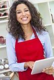 使用片剂计算机的妇女烹调在厨房 免版税库存图片
