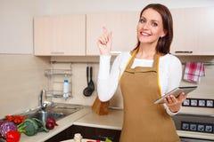 使用片剂计算机的妇女烹调 库存图片