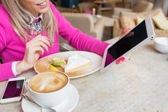 使用片剂计算机的妇女,当喝蛋糕和咖啡在咖啡馆时 免版税库存照片