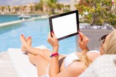 使用片剂计算机的妇女,当放松由游泳池时 免版税库存图片
