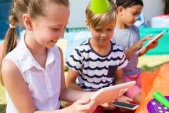 使用片剂计算机的孩子在生日聚会期间 免版税库存图片