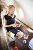 使用片剂计算机的富裕的妇女在私人喷气式飞机 库存图片