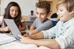 使用片剂计算机的小学男孩在学校课程 库存照片