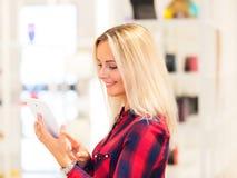 使用片剂计算机的少妇在时尚商店 免版税库存照片
