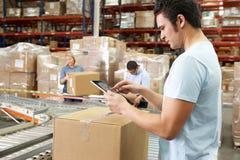使用片剂计算机的工作者在配给物仓库 免版税库存图片