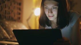 使用片剂计算机的年轻可爱的妇女特写镜头在家说谎的夜间在床 免版税库存照片