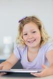使用片剂计算机的微笑的女孩在桌 免版税库存图片