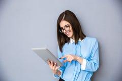 使用片剂计算机的微笑的女实业家 免版税库存照片
