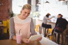 使用片剂计算机的微笑的年轻白肤金发的妇女,当坐用奶昔时 免版税库存照片