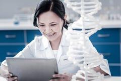 使用片剂计算机的快乐的基因科学家在实验室 免版税库存照片