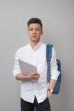 使用片剂计算机的愉快的偶然亚裔男学生隔绝了o 免版税库存照片