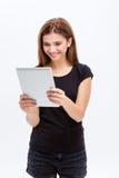 使用片剂计算机的愉快的可爱的逗人喜爱的少妇 免版税图库摄影