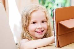 使用片剂计算机的愉快的小女孩 免版税库存照片