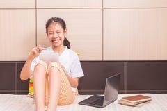 使用片剂计算机的愉快的微笑的亚裔女孩学习 免版税库存图片
