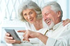 使用片剂计算机的愉快的年长夫妇 图库摄影