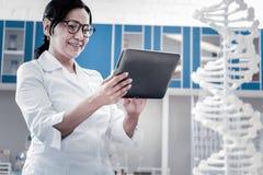 使用片剂计算机的放光的女性科学家在实验室 库存照片