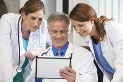 使用片剂计算机的男女住院医生 免版税库存图片