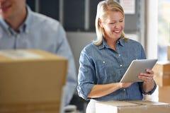 使用片剂计算机的经理在配给物仓库 免版税图库摄影