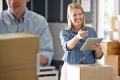 使用片剂计算机的经理在配给物仓库 免版税库存图片