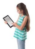 使用片剂计算机的美丽的青春期前的女孩 免版税库存图片