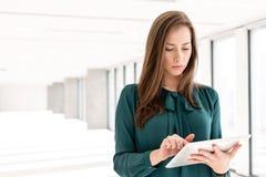 使用片剂计算机的美丽的年轻女实业家在新的办公室 免版税库存图片
