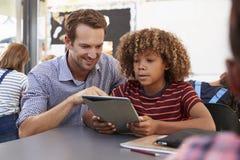 使用片剂计算机的老师和男小学生在类 图库摄影