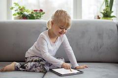 使用片剂计算机的聪明的小女孩,当在家时坐长沙发在客厅 免版税库存照片