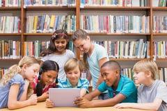 使用片剂计算机的逗人喜爱的学生在图书馆 库存图片