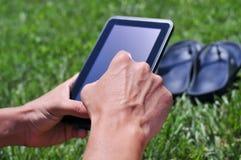 使用片剂计算机的年轻人在公园 免版税库存照片