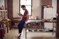 使用片剂计算机的年轻人在厨房,全长 免版税库存图片
