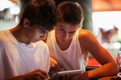 使用片剂计算机的年轻人在咖啡馆 免版税图库摄影