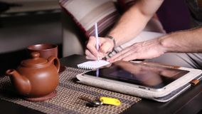 使用片剂计算机的年轻商人在笔记本的网上购物和制造笔记的 工作在个人计算机片剂的人和 影视素材