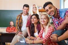 使用片剂计算机的年轻学生团体,混合的族种人微笑的看对照相机 免版税库存照片