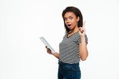 使用片剂计算机的年轻非洲妇女和有一个想法 免版税库存照片