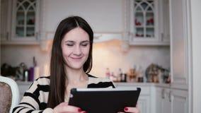 使用片剂计算机触摸屏幕的一名美丽的年轻深色的妇女的画象在一明亮用餐 影视素材