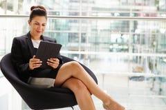 使用片剂计算机,四分之三长度的女实业家 免版税图库摄影