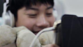 使用片剂计算机,年轻十几岁的男孩的逗人喜爱的亚裔男孩观看在数字片剂 E 股票录像