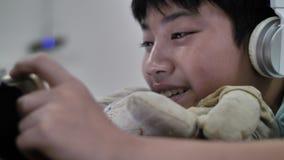 使用片剂计算机,年轻十几岁的男孩的逗人喜爱的亚裔男孩观看在数字片剂 E 影视素材