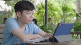 使用片剂计算机,年轻十几岁的男孩的逗人喜爱的亚裔男孩默默地做在数字片剂的家庭作业有面孔的 股票视频
