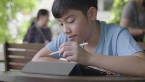 使用片剂计算机,年轻十几岁的男孩的逗人喜爱的亚裔男孩默默地做在数字片剂的家庭作业有面孔的 股票录像